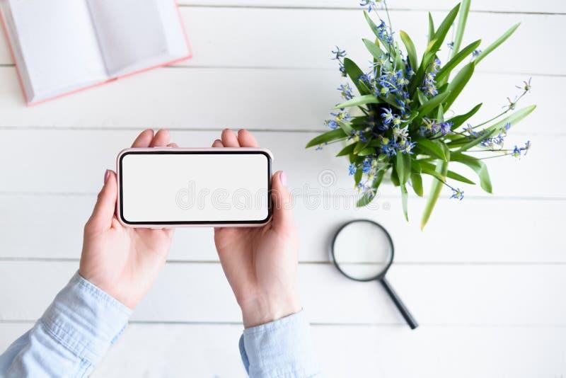 M?os f?meas com um smartphone Tela vazia branca Tabela com caderno e flores no fundo fotografia de stock royalty free