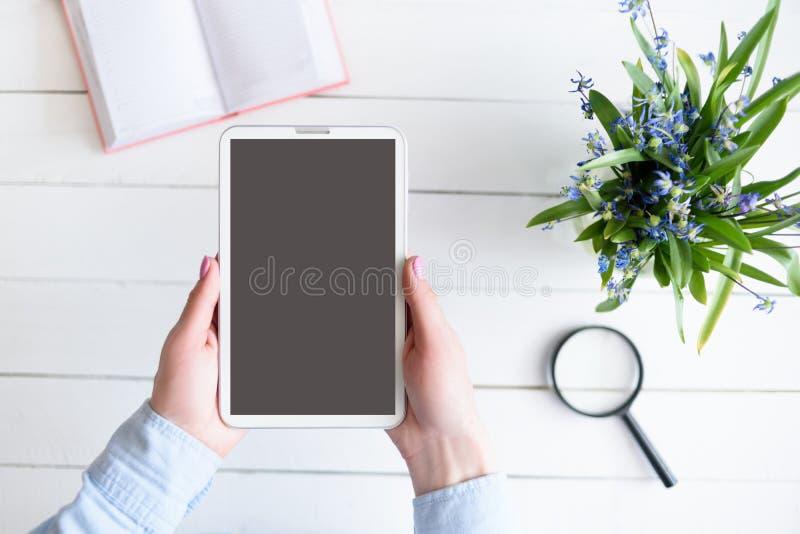 M?os f?meas com uma tabuleta Tela vazia preta Tabela com caderno e flores no fundo fotos de stock royalty free
