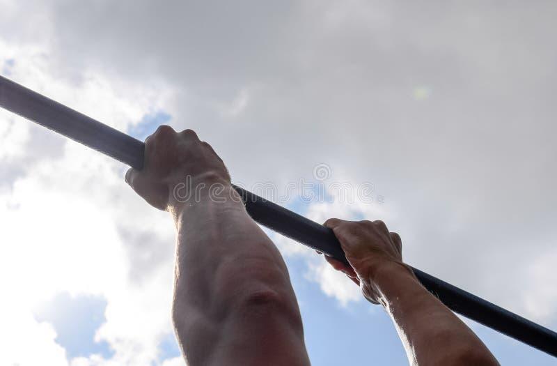 M?os no close-up da barra O homem puxa-se acima na barra Jogando esportes no ar fresco imagem de stock