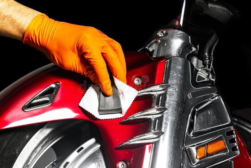 M?os polonesas do trabalhador da cera do carro que aplicam a fita protetora antes de lustrar Motocicleta lustrando e de lustro De imagens de stock royalty free