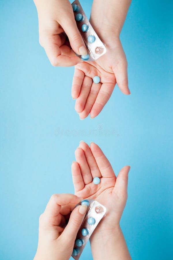 M?os que abrem um pacote de comprimidos azuis contra um fundo azul imagem de stock