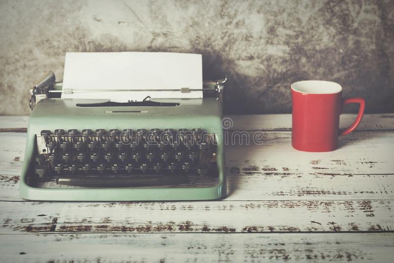 M?quina de escribir vieja al lado de una taza de caf? fotografía de archivo