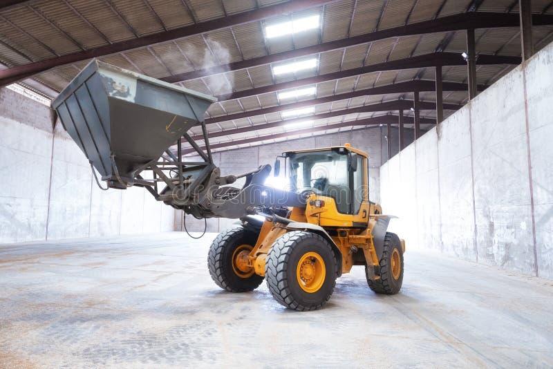 M?quina escavadora do carregador da roda Máquina da construção no hangar foto de stock