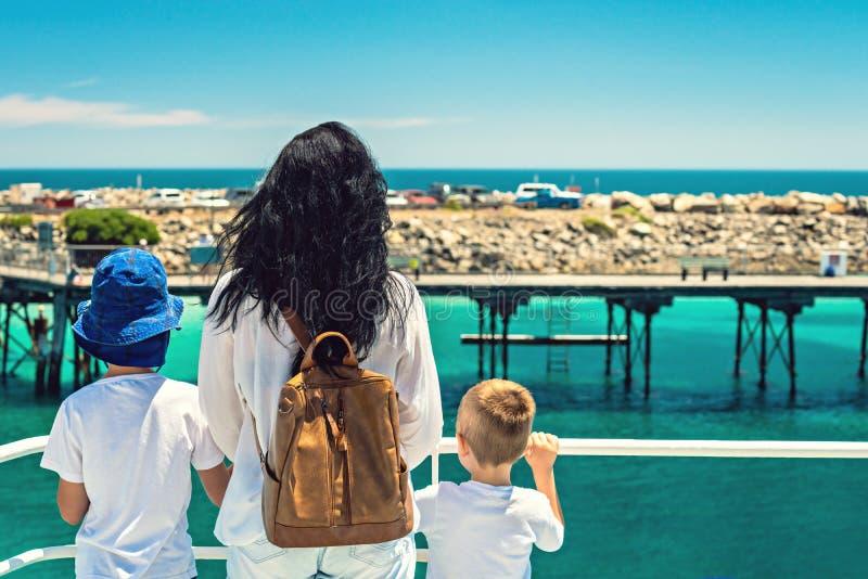 M?re avec ses fils se tenant sur la plate-forme de ferry images stock