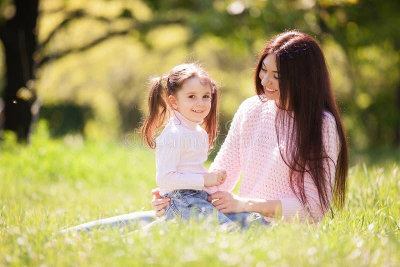 M?re et fille heureuses en parc d'?t? Sc?ne de nature de beaut? avec le mode de vie ext?rieur de famille Famille heureuse se repo photo libre de droits