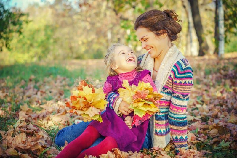M?re et fille jouant en parc d'automne image stock