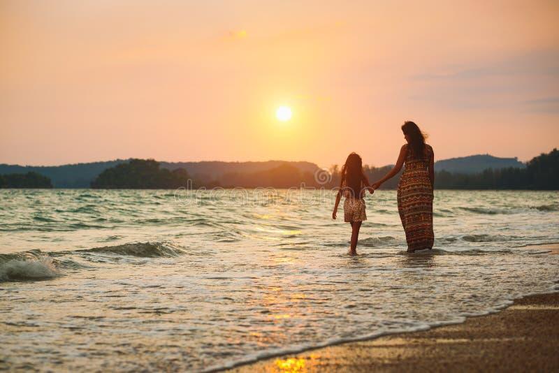 M?re et fille marchant sur la plage avec le coucher du soleil photographie stock