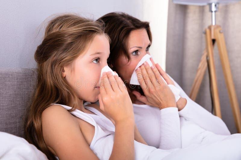 M?re et fille soufflant leur nez avec le mouchoir images libres de droits