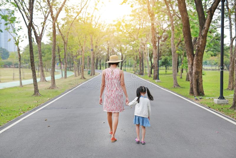 M?re et sa fille marchant sur la route et tenant des mains dans le jardin ext?rieur de nature Vue arri?re image libre de droits