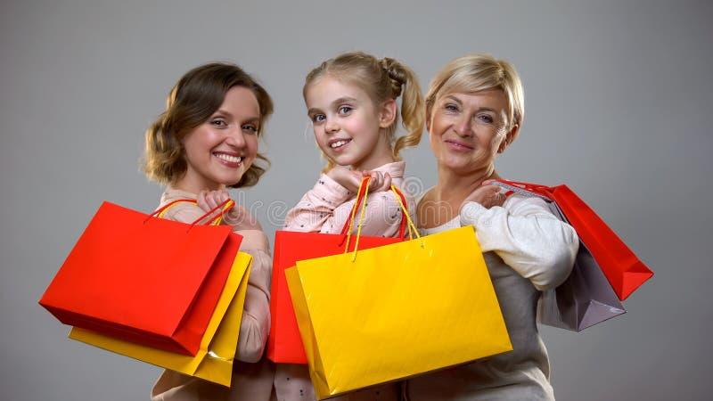 M?re, fille heureuse et mamie tenant des sacs ? provisions, loisirs femelles, vente photo libre de droits