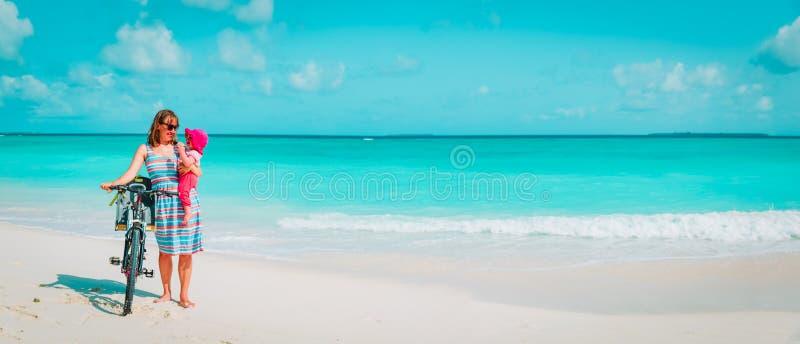 M?re heureuse avec le petit v?lo mignon de b?b? ? la plage photos libres de droits