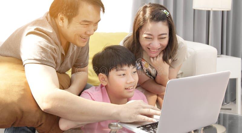 M?re heureuse et fils de p?re de famille observant sur l'ordinateur portable images libres de droits