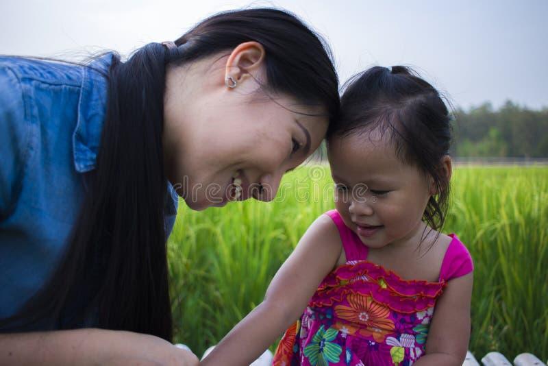 M?re heureuse et son enfant jouer avoir dehors l'amusement, la terre arri?re de gisement vert de riz photos stock