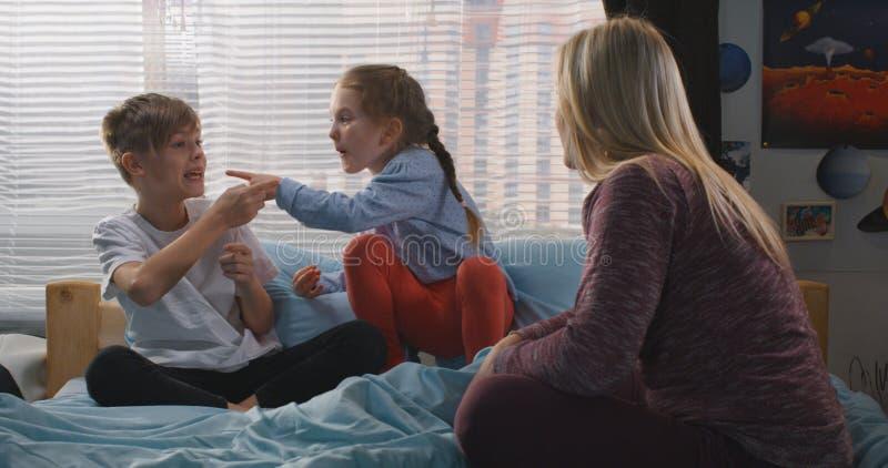 M?re parlant avec les enfants de m?mes parents se querellants photographie stock