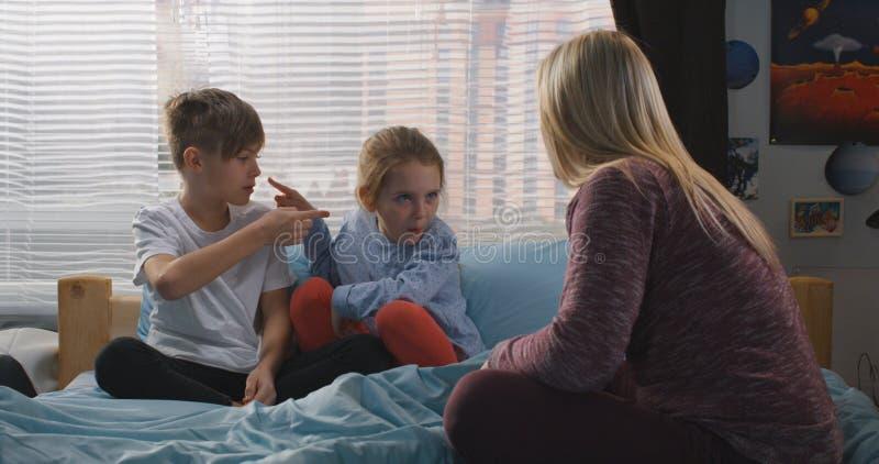 M?re parlant avec les enfants de m?mes parents se querellants photo libre de droits