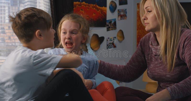 M?re parlant avec les enfants de m?mes parents se querellants photo stock