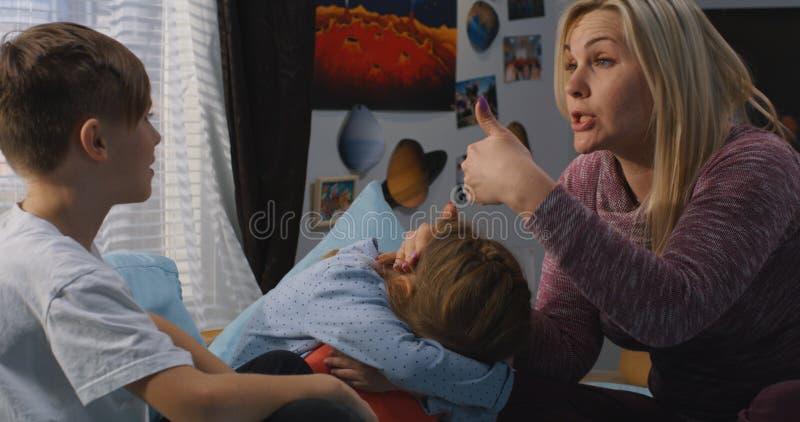 M?re parlant avec les enfants de m?mes parents se querellants image libre de droits
