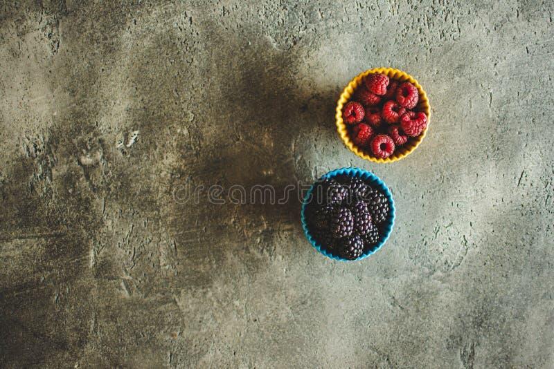 M?res et framboises dans des cuvettes en c?ramique sur le fond en pierre rustique photos stock