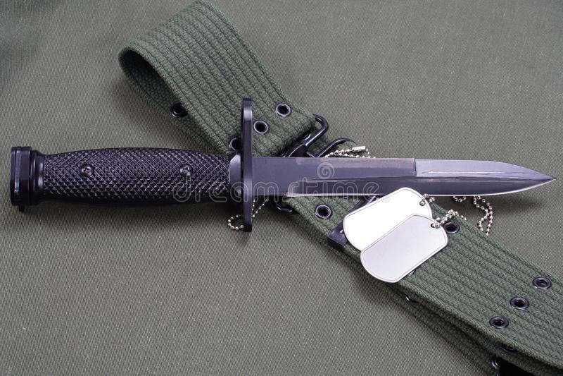 M16 rifle bayonet on uniform. Background royalty free stock image