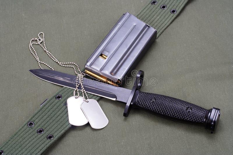 M16 rifle bayonet on uniform. Background royalty free stock photography