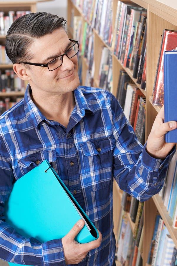 Mûrissez l'étudiant mâle étudiant dans la bibliothèque images libres de droits