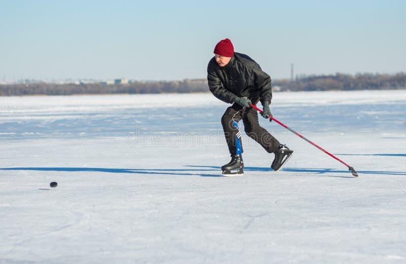 Mûrissez l'homme essayant désespérément de rattraper le paquet tout en jouant l'hockey sur une rivière congelée Dniepr en Ukraine photographie stock libre de droits