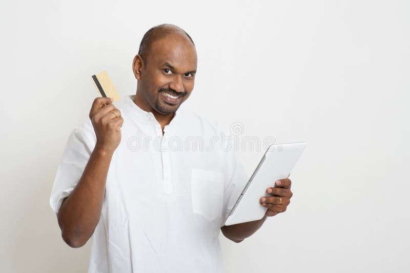 Mûrissez l'homme indien d'affaires occasionnelles à l'aide du PC de comprimé et de la voiture de crédit photographie stock