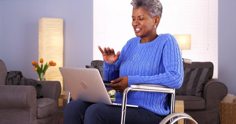 Mûrissez la femme africaine s'asseyant dans le fauteuil roulant avec l'ordinateur portable photos stock