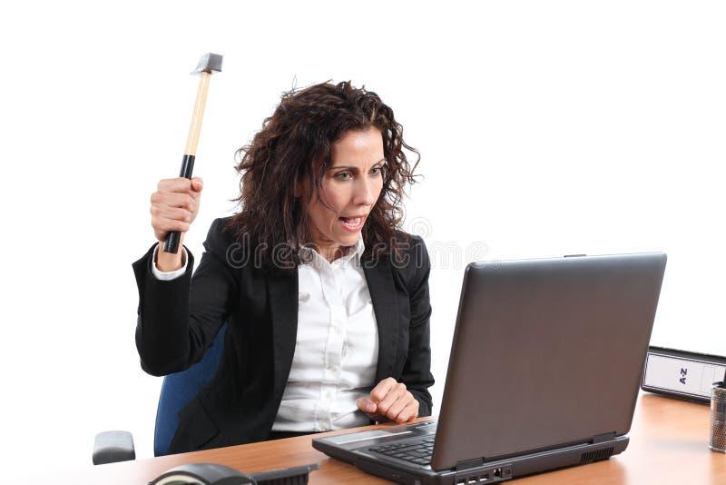Mûrissez la femme d'affaires essayant de détruire un ordinateur portable avec un marteau image stock