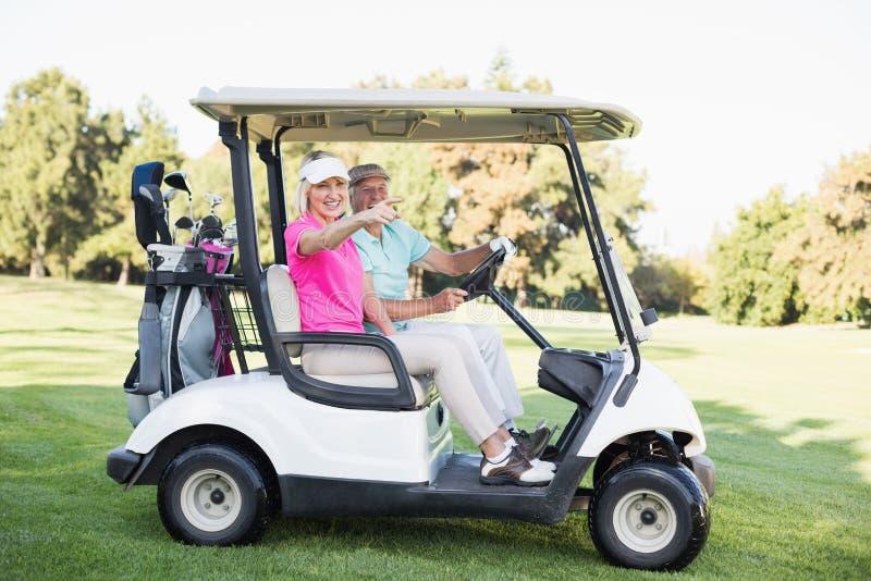 Mûrissez la femme se dirigeant tout en se reposant dans le boguet de golf images libres de droits