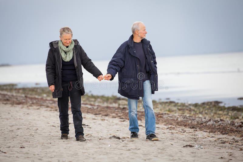 Mûrissez les couples heureux marchant sur la plage en automne photographie stock