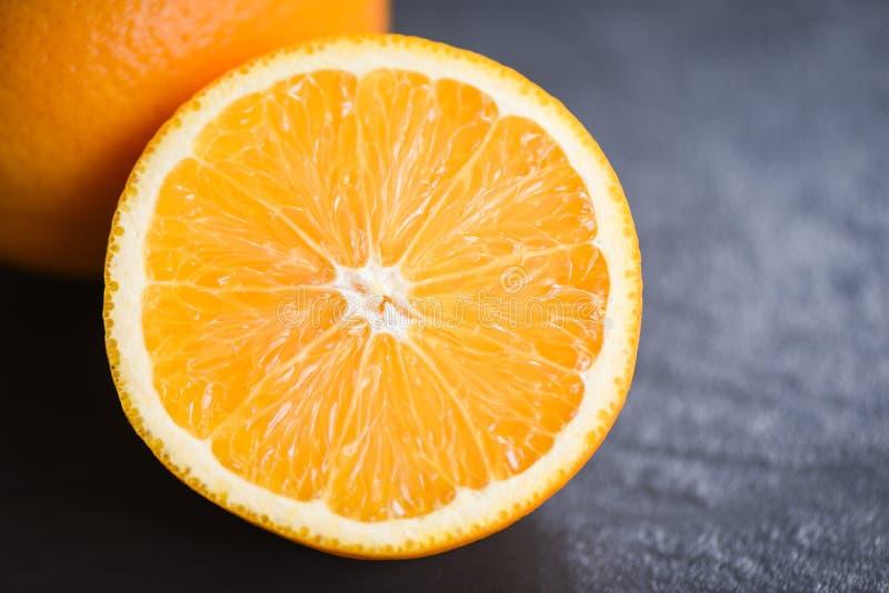 M?rk bakgrund f?r ny orange fruktskivahalva arkivfoto