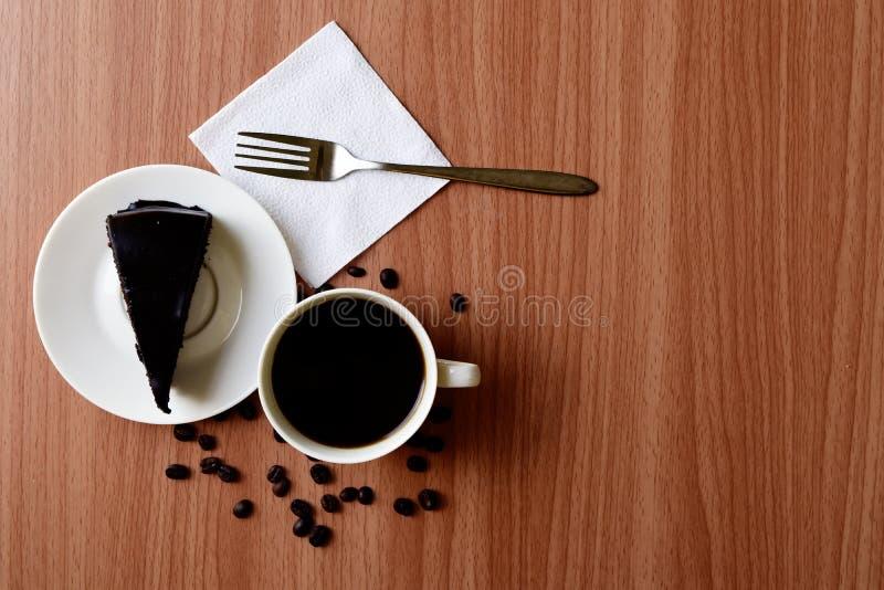 M?rk choklad- och kopp kaffeespresso p? tefatet p? tr?tabellen royaltyfria bilder