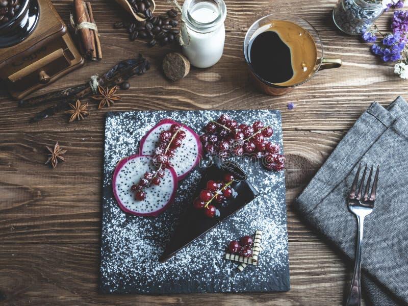 M?rk chokladkaka mozart, r?d vinb?r p? tabellen en kopp kaffe, kr?m royaltyfria bilder