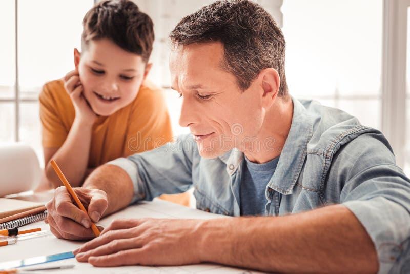 M?rker-haired fader som drar geometriska diagram tillsammans med hans adoptiv- barn fotografering för bildbyråer