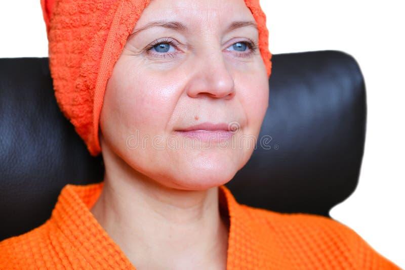 M?scara cosm?tica en la cara Retrato ascendente cercano de la mujer joven hermosa con la toalla en su cabeza que tiene procedimie imagen de archivo