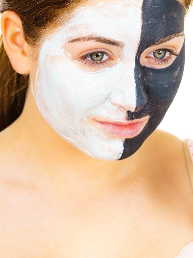 A m?scara do preto da menina na meia cara aplica a lama branca fotos de stock royalty free
