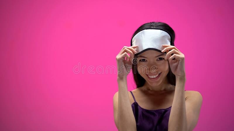 M?scara flertando e vestindo da mulher asi?tica nova de olho, isolada no fundo cor-de-rosa imagem de stock