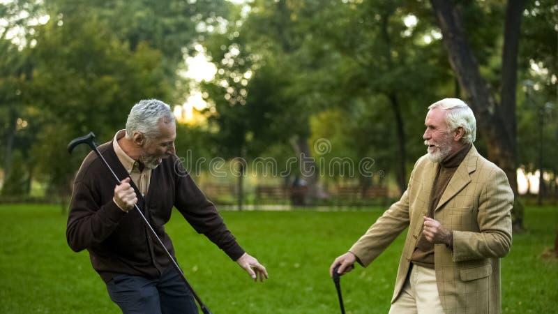 M?scy emeryci tanczy parka z chodz?cymi kijami, przyja?? humor, mie? zabaw? obrazy stock