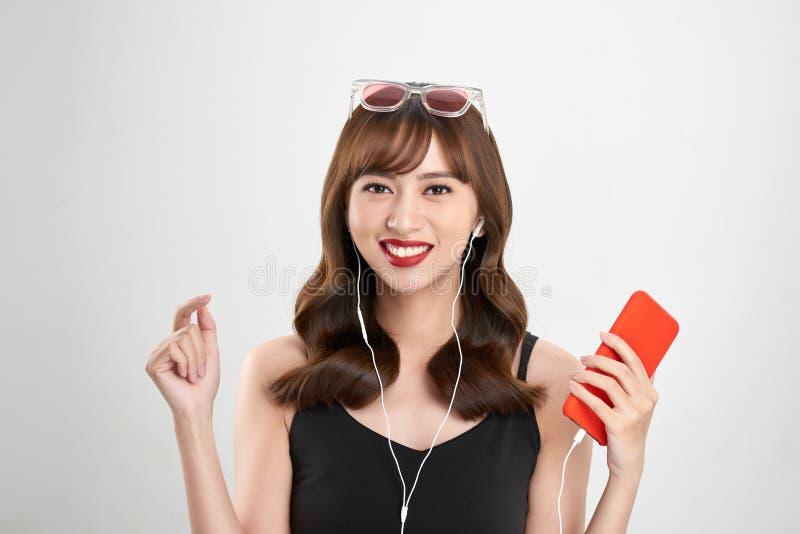 M?sica Baile de la mujer con los earbuds/los auriculares que escuchan la m?sica en el jugador mp3 imagen de archivo