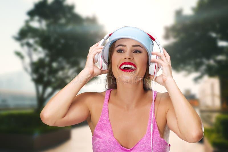 M?sica que escucha de la mujer joven en auriculares fotografía de archivo libre de regalías