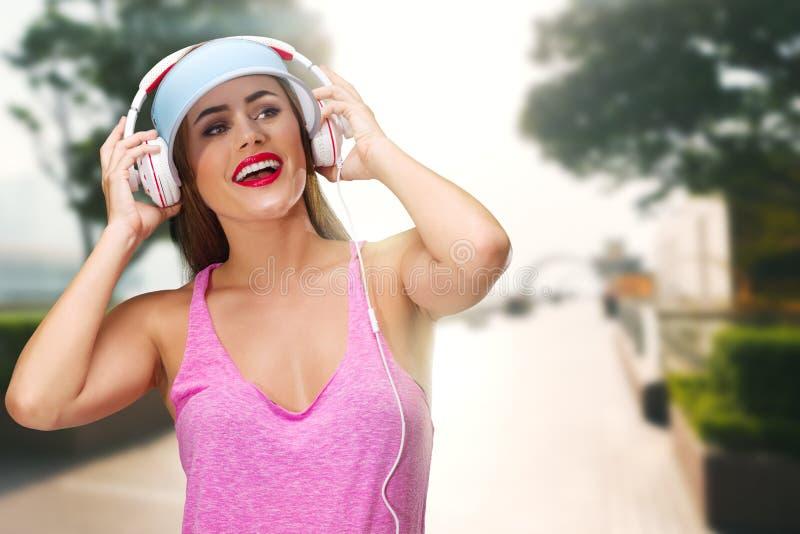 M?sica que escucha de la mujer joven en auriculares imagen de archivo