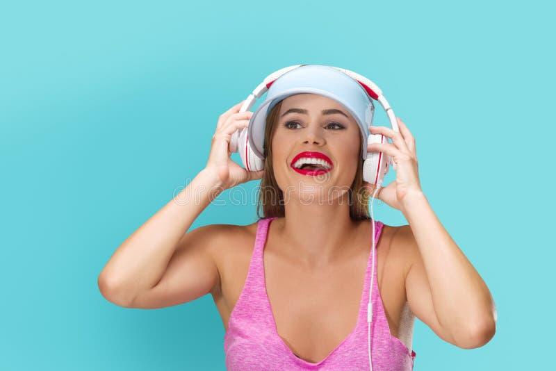 M?sica que escucha de la mujer joven en auriculares imagen de archivo libre de regalías