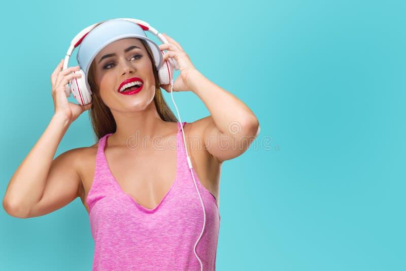 M?sica que escucha de la mujer joven en auriculares imagenes de archivo