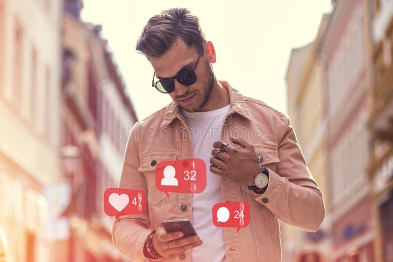 M?sica que escucha del hombre adulto joven en Smartphone y auricular en la calle en el tiempo de verano fotos de archivo