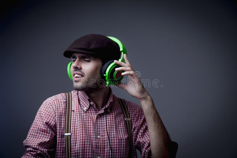 M?sica retro Retrato do homem considerável DJ com os olhos fechados no desgaste denominado retro elegante e nos fones de ouvido O imagens de stock royalty free
