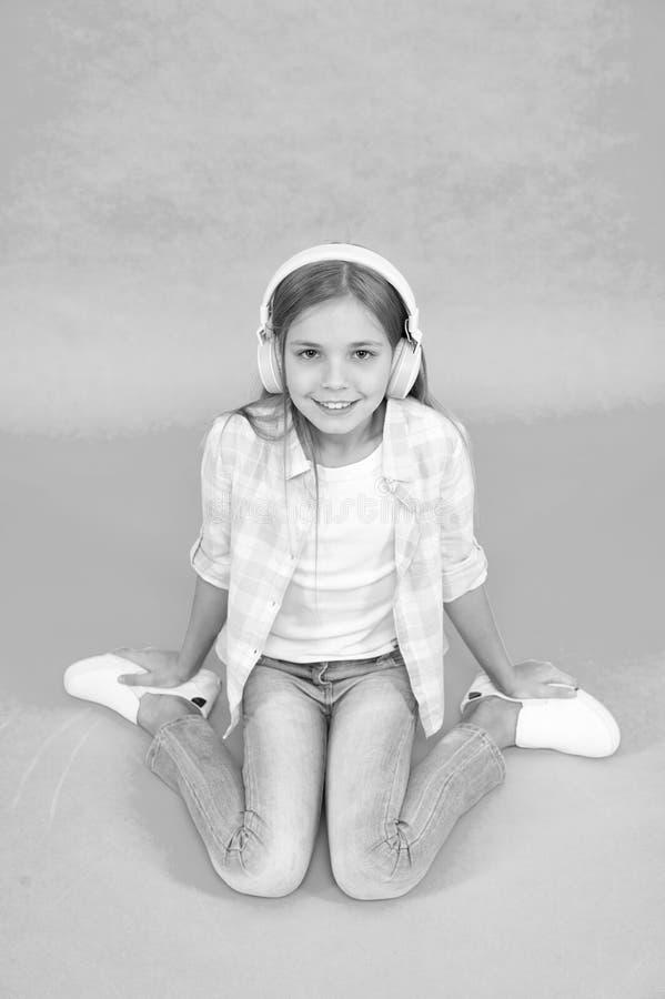 M?sica sempre comigo Conceito do lazer A menina escuta fones de ouvido da m?sica Aprecie a trilha da faixa favorita Crian?a da me imagens de stock