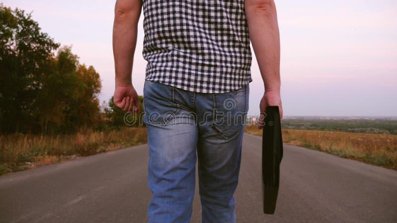 M?ski biznesmen w szkockiej kraty koszula chodzi wzd?u? asfaltowej drogi z czarn? teczk? z dokumentami w r?ce Zako?czenie zdjęcie royalty free