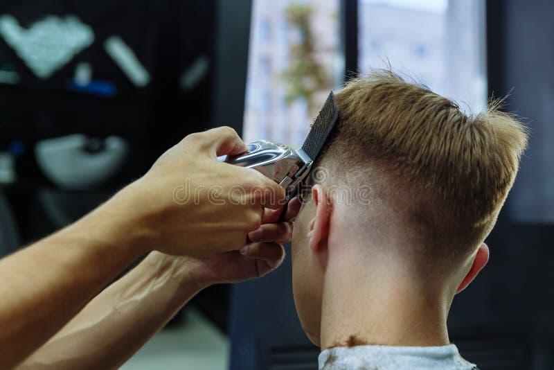 M?ski ostrzy?enie z elektryczn? ?yletk? Fryzjer męski robi ostrzyżeniu dla klienta przy fryzjera męskiego sklepem używać hairclip zdjęcie royalty free
