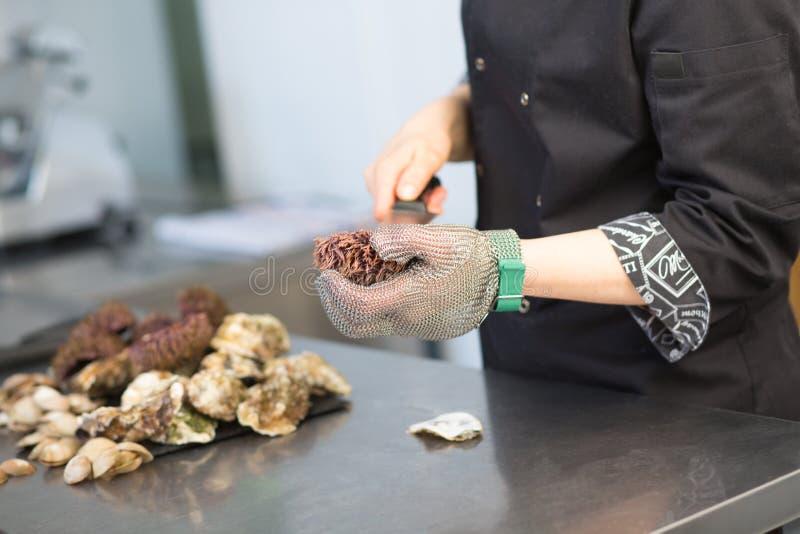 M?starklass Kocken klipper havsgatubarnet i köket av en restaurang Closeup av en hand med en kniv i en metallhandske P? en metall royaltyfri fotografi